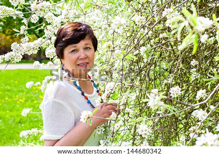 Portrait of beautiful senior woman in the spring blossom - stock photo