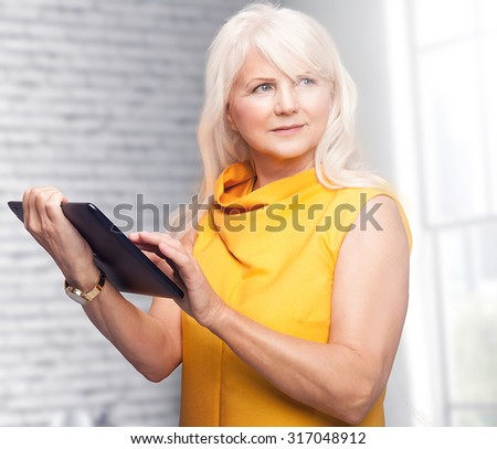 Portrait of beautiful senior woman using tablet. Lady with long grey hair. - stock photo
