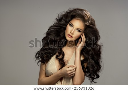 Portrait of beautiful sensual brunette woman with long curly hair. Beauty photo. - stock photo