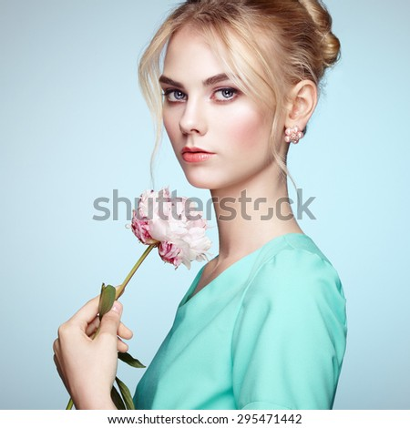 Portrait of beautiful sensual woman with elegant hairstyle.  Perfect makeup. Blonde girl. Fashion photo. Flowers - stock photo