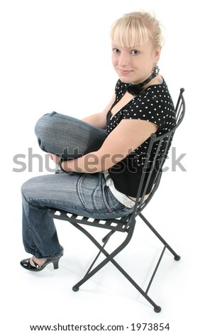 Portrait of beautiful seventeen year old girl.  Natural beauty, no make-up.  Sitting in black iron chair.
