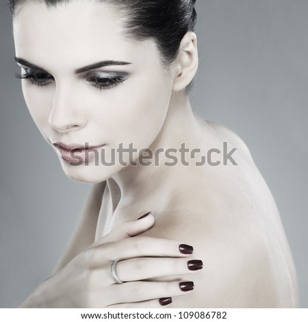 Portrait of beautiful sexual brunette on a grey background, emotions, cosmetics - stock photo