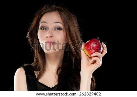 Portrait of beautiful sexy brunette girl on a black background with an apple - stock photo
