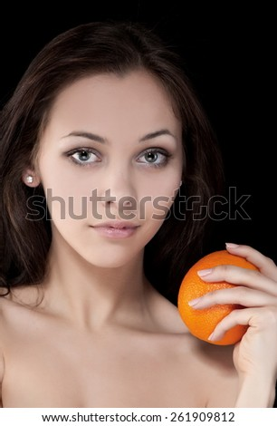 Portrait of beautiful sexy brunette girl on a black background with orange - stock photo