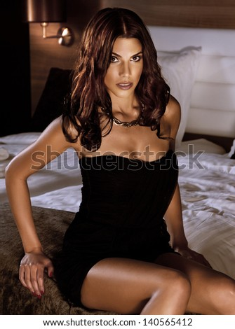 Portrait of beautiful sexy brunette woman sitting in bedroom wearing elegant black dress, looking at camera. - stock photo