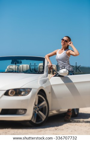 Portrait of beautiful sexy fashion woman model in sunglasses sitting in luxury white car with sea and sky background. Young woman driving on road trip on sunny summer day. Sea and sky. White cabrio.