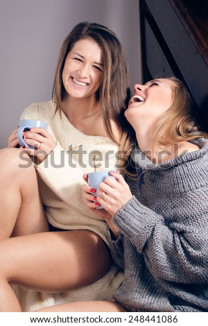 Portrait of 2 beautiful sexy women happy smiling girl friends having fun sitting in a sweaters on a blanket with hot drink looking at camera  - stock photo