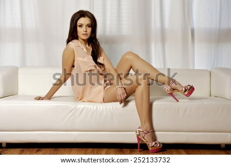 Portrait of beautiful sexy young adult attractive and sensuality pretty brunette woman in pink blouse lying on the sofa in luxury style apartment - stock photo