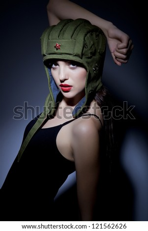 Portrait of beautiful sexy young woman with russian tank cap posing over blue shadow background.