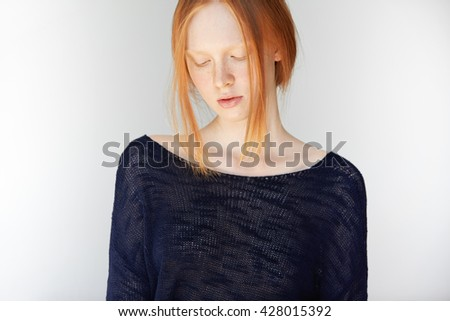 Portrait of beautiful slim young woman with ginger hair and perfect healthy skin with freckles, wearing black top, looking down with shy expression on her face against white copy space studio wall - stock photo