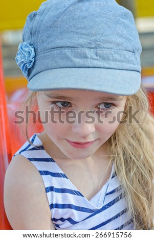 Portrait of beautiful small girl in denim cap and striped clothes posing outdoors - stock photo
