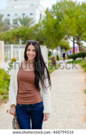 Portrait of beautiful smiling active woman walking outdoors background