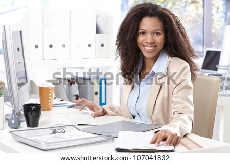 Portrait of beautiful smiling afro-american office worker sitting at desk, using computer. - stock photo