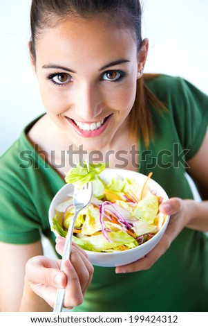 Portrait of beautiful smiling and happy Caucasian woman enjoying a healthy salad - stock photo