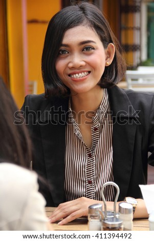 Portrait of beautiful smiling Asian business woman sitting in a cafe - stock photo