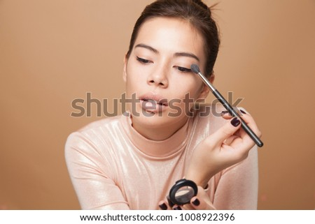 Portrait of beautiful smiling Asian woman applying a eyeshadow .Perfect soft makeup. Skin care Cosmetics concept. Freckles face. High resolution,studio shot, horizontal.