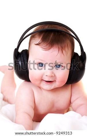 portrait of beautiful smiling baby with earphones - stock photo