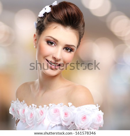 Portrait of beautiful smiling  bride in wedding dress over art background - stock photo