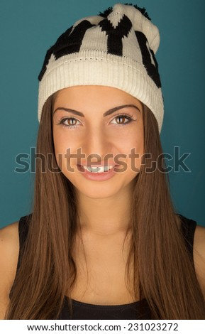Portrait of beautiful smiling brown-haired woman in winter hat and shirt on a blue background