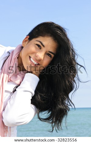 Portrait of beautiful smiling brunette girl at beach being playful