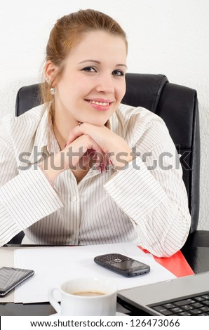 Portrait of beautiful smiling business woman sitting in her office. - stock photo