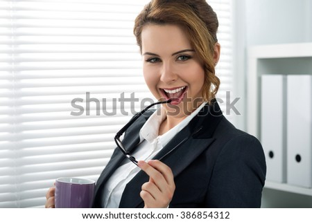 Portrait of beautiful smiling businesswoman put glasses in mouth standing in office holding cup of beverage. Successful woman in suit. Business, exchange market, job offer, excellent education concept - stock photo