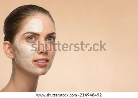 Portrait of beautiful smiling girl in spa with cosmetic cream on her face with clean and  fresh skin looking aside isolated on beige background  with copy place - stock photo