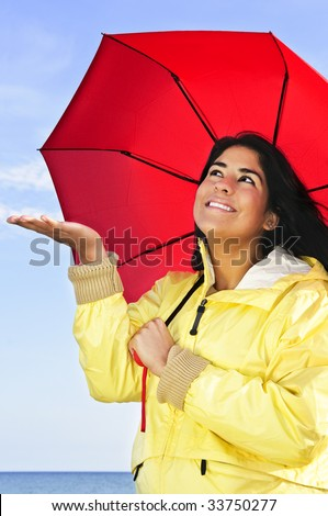 Portrait of beautiful smiling girl wearing yellow raincoat holding red umbrella checking for rain