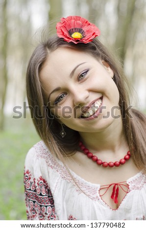 Portrait of  beautiful smiling girl with flower of poppy in hair