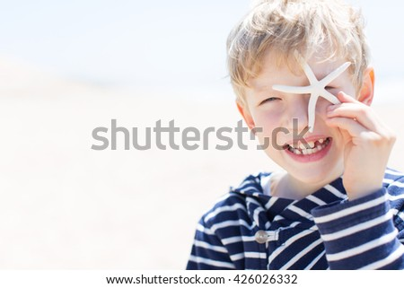 portrait of beautiful smiling happy boy winking and covering his eye with starfish at the beach, vacation and lifestyle concept, copyspace on the side