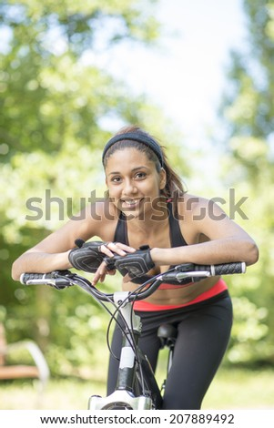 Portrait of beautiful smiling latin athletic woman with bike, healthy life concept.