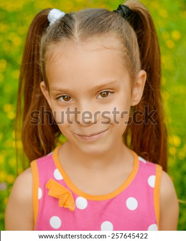 Portrait of beautiful smiling little girl in green summer city park.