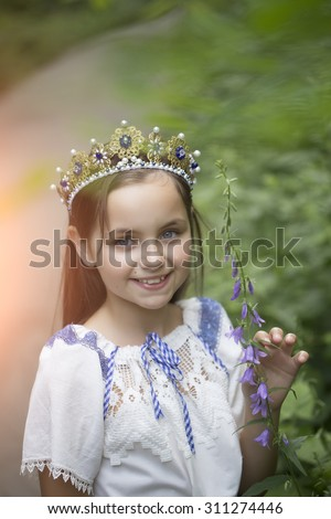 Portrait of beautiful smiling princess girl with long brunette hair in traditional ukrainian embroidery white blue colors and beautiful diadem with diamonds in gold outdoor, vertical picture - stock photo