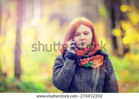 Portrait of beautiful smiling red-haired woman talking by mobile phone (shallow dof) - stock photo