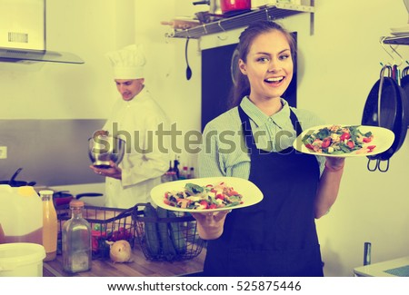Portrait of beautiful smiling woman waitress wearing apron and holding ready to serve salad