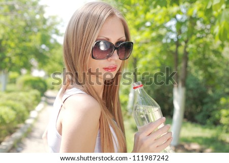 Portrait of beautiful smiling woman with bottle of water, outdoors, summer - stock photo