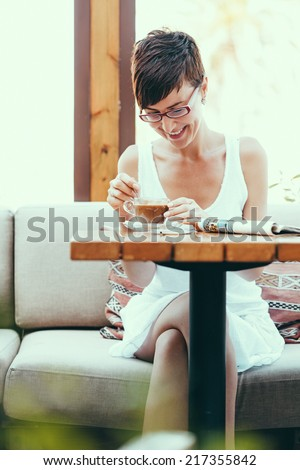 portrait of beautiful smiling women in coffee shop, mixing her coffee drink. - stock photo
