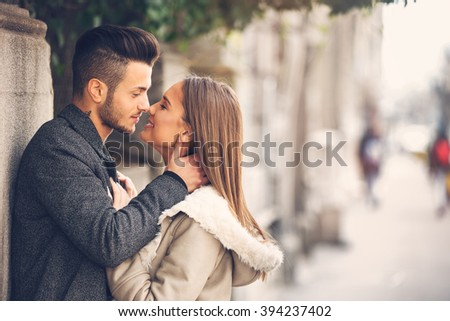 Portrait of beautiful smiling young couple outside, side view face to face. Happy couple in love outdoor on street.Added photo filter and grain/noise. - stock photo