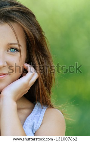 Portrait of beautiful smiling young woman close up, against background of summer green park. - stock photo