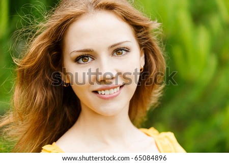 Portrait of beautiful smiling young woman close up. Against green summer garden. - stock photo