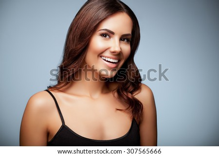 portrait of beautiful smiling young woman in black tank top clothing, on grey background