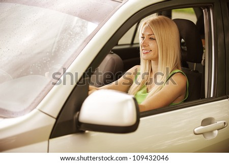 Portrait of beautiful smiling young woman in car. - stock photo
