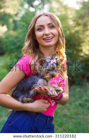 Portrait of beautiful smiling young woman with small dog outdoor - stock photo