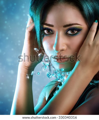 Portrait of beautiful snow queen over snowy background, trendy blue green hair color, Christmas makeup ideas, fashion look for New Year holidays - stock photo