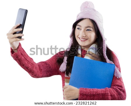 Portrait of beautiful student taking self portrait with a smart phone while wearing a knitted clothes and holding a folder
