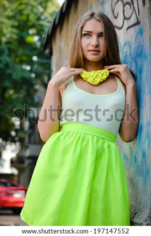 portrait of beautiful stylish fashion young woman at graffiti wall happy smiling & looking at camera on city urban summer or spring outdoors background image - stock photo
