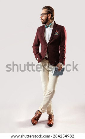Portrait of beautiful stylish young bearded man in a burgundy jacket and bow tie with book in hand - stock photo
