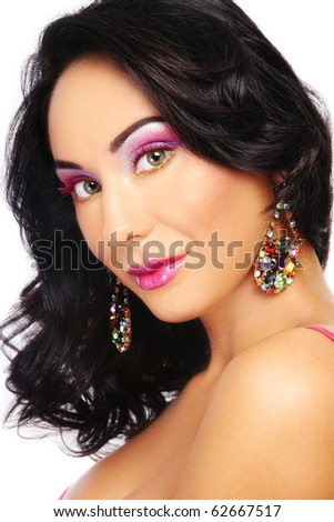 Portrait of beautiful tanned sexy brunette with bright makeup and sparkly earrings