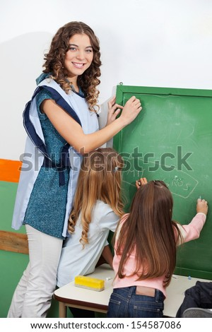Portrait of beautiful teacher and children writing on chalkboard in classroom - stock photo