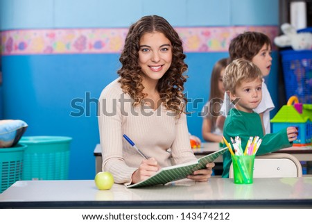 Portrait of beautiful teacher writing in book with children playing in background - stock photo